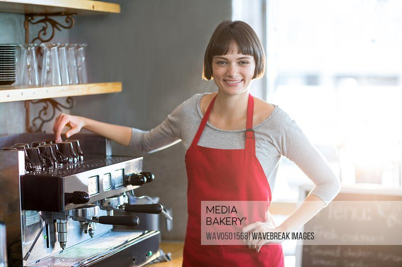 Portrait of smiling waitress standing with hand on hip at cafA?