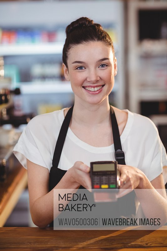 Smiling waitress showing credit card machine in cafe