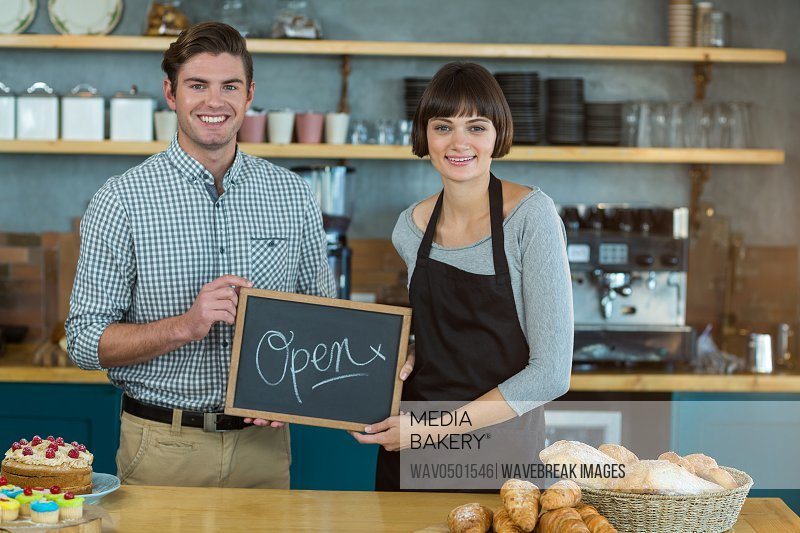 Portrait of man and waitress holding slate with open sign in cafe