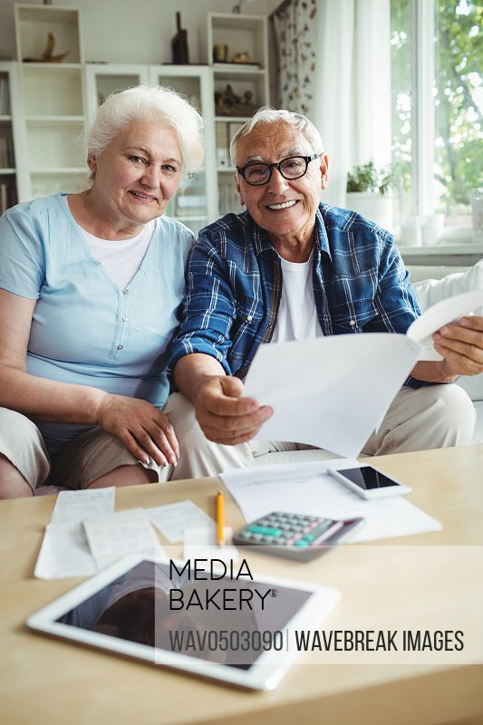 Senior couple smiling while checking the bills at home