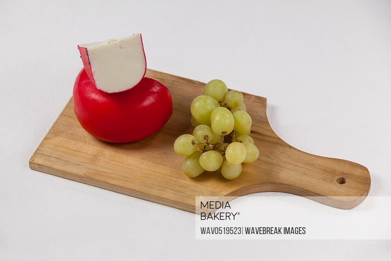 Red cheese and grapes on wooden board