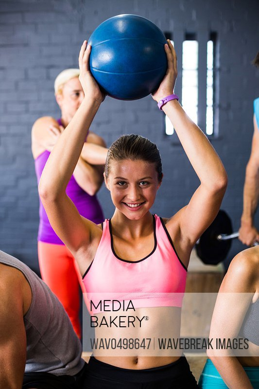 Portrait of pretty woman exercising with fitness ball in gym