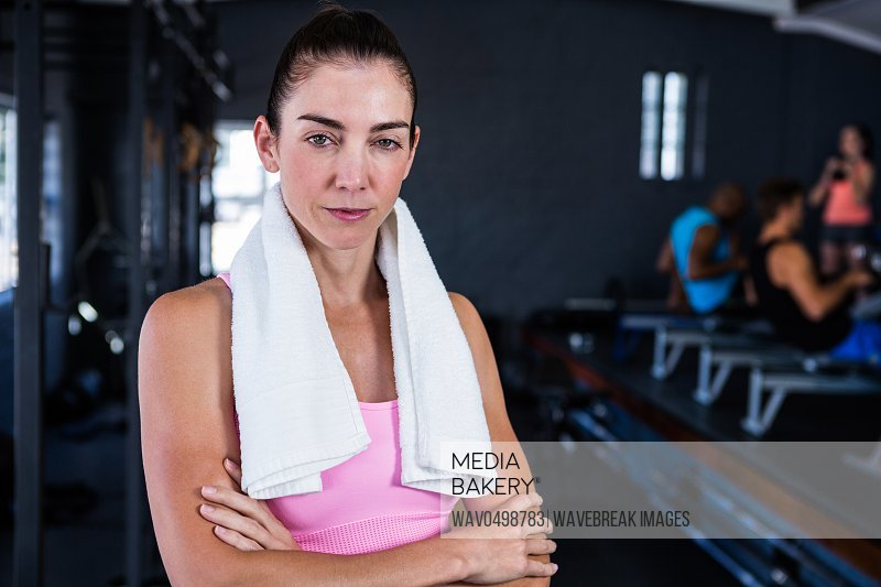 Portrait of serious female athlete with arms crossed while standing in gym