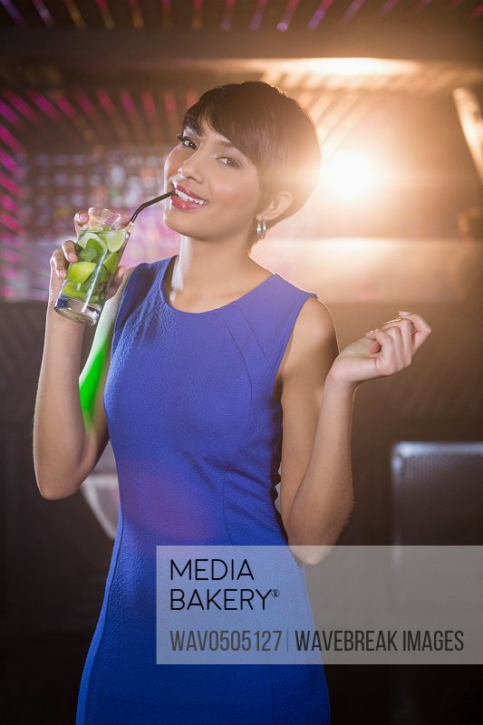 Portrait of young woman dancing on dance floor while having cocktail in bar