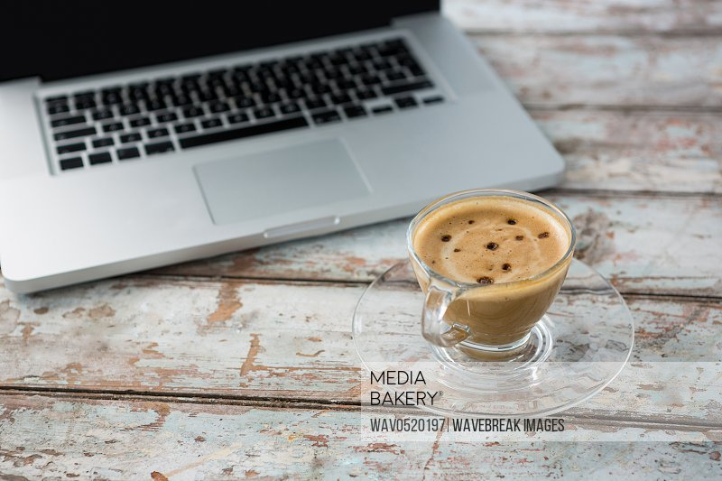Cup of coffee and laptop on wooden table