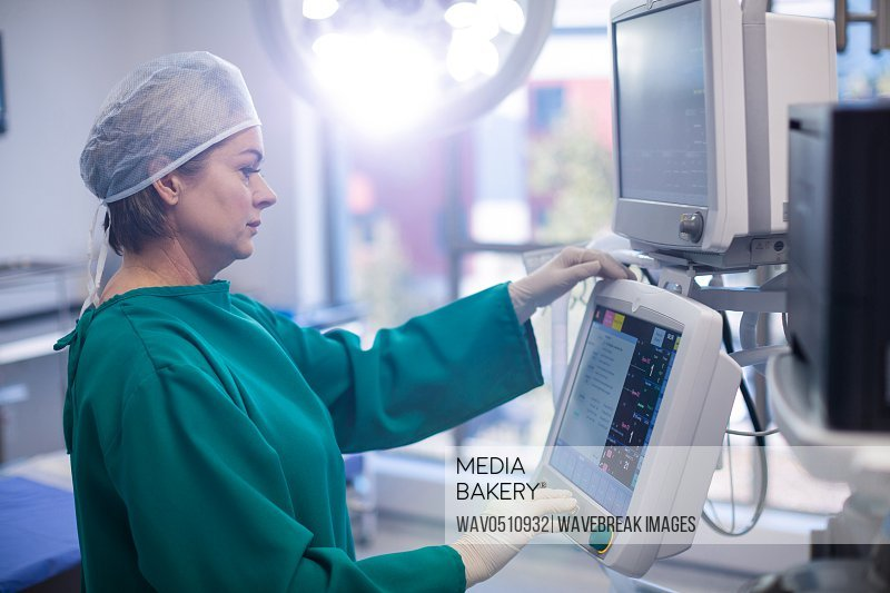 Female surgeon looking at monitor in operation room at hospital