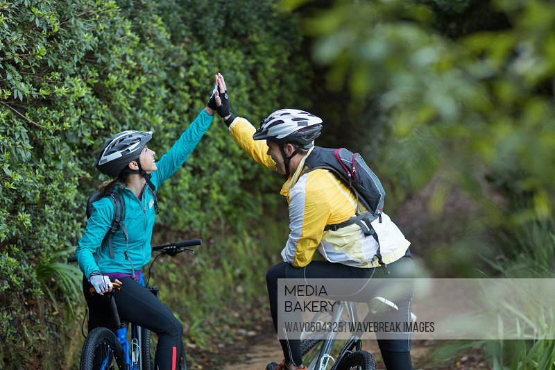 Happy biker couple giving high five while riding bicycle in countryside