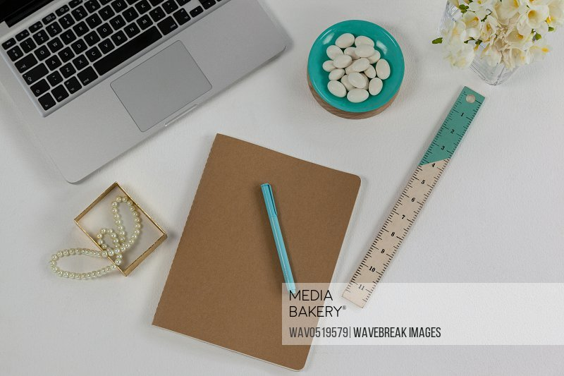 Laptop pearl necklace ruler pen diary and pebbles
