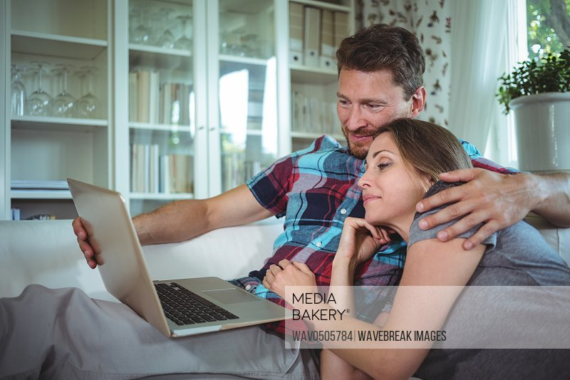 Happy couple using laptop in living room at home