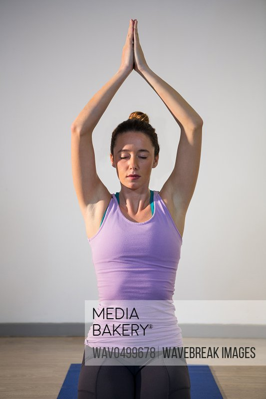 Woman sitting in lotus pose with eyes closed in fitness studio