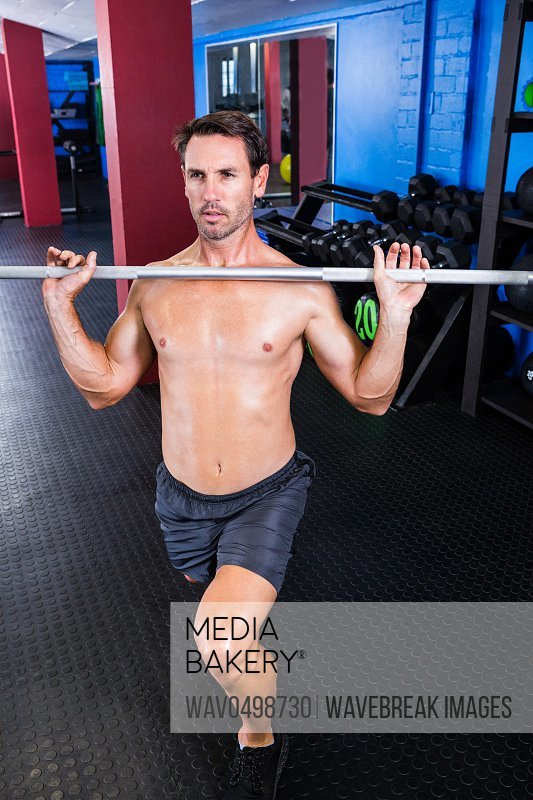 Male athlete lifting barbell in gym