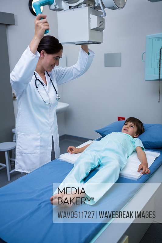 Female doctor adjusting x-ray machine on patient at hospital