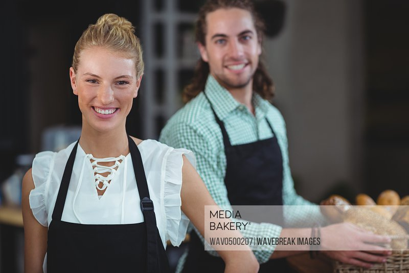 Portrait of waiter and waitress working behind the counter in cafe