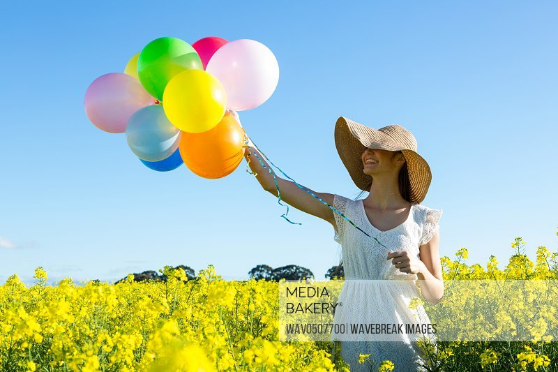 Woman holding colorful balloons in mustard field on a sunny day