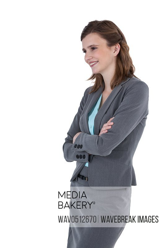 Smiling businesswoman with arms crossed standing against white background