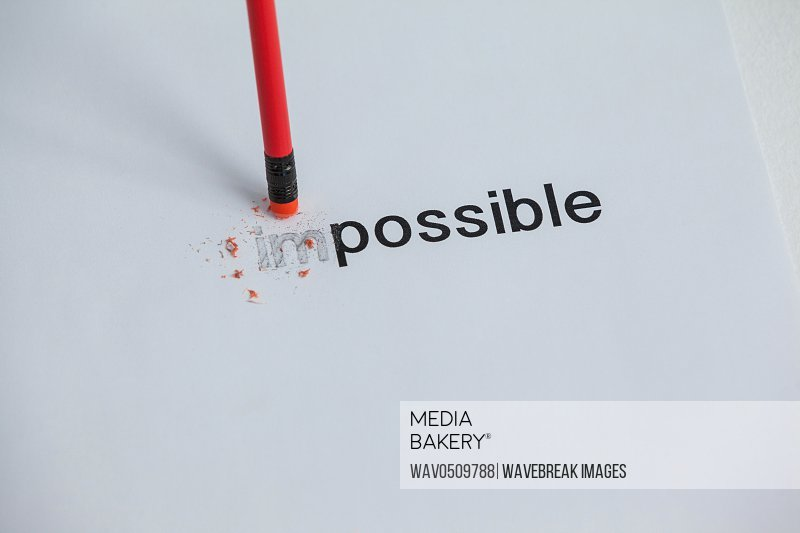 Changing the word impossible to possible with a pencil eraser on paper