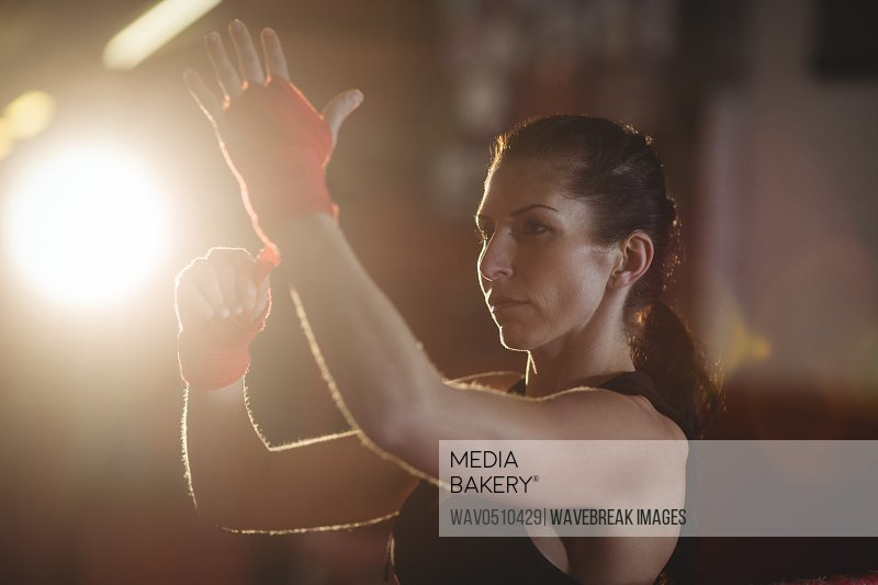 Female boxer wearing red strap on wrist in fitness studio