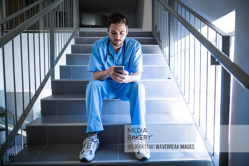 Male nurse sitting on staircase and using mobile phone of hospital
