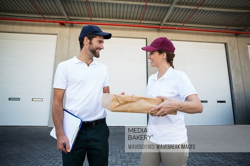 Happy delivery man and woman standing with clipboard and parcel outside the warehouse
