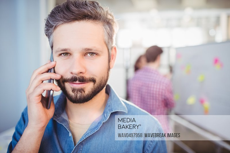 Portrait of confident young businessman listening to cellphone at creative office