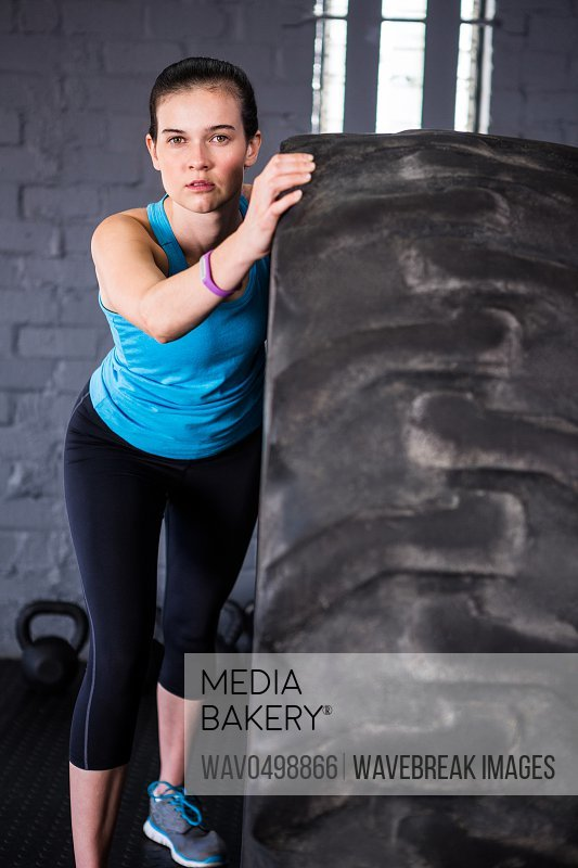 Portrait of confident female athlete pushing tire while exercising in gym