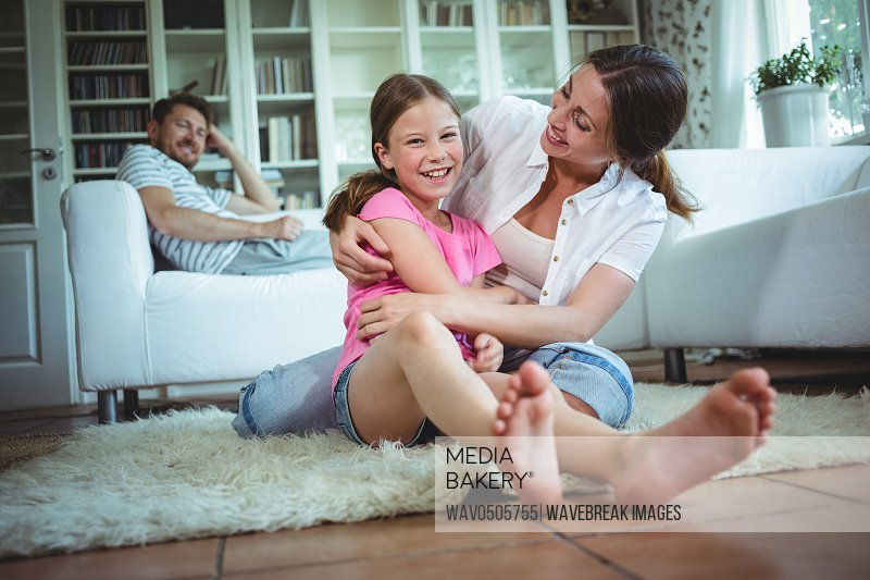 Happy mother and daughter sitting on the floor and embracing
