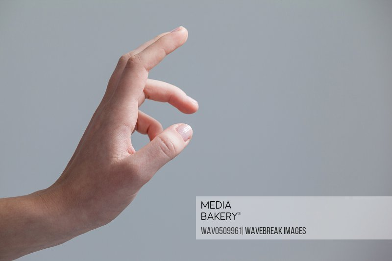 Close-up of hand of a woman making gestures against grey background