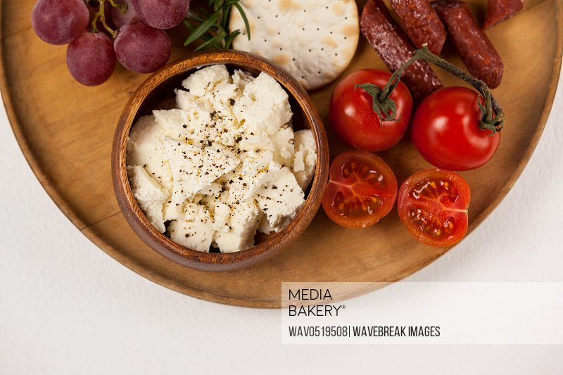 Crispy biscuits cherry tomatoes grapes and bowl of cheese on wooden board