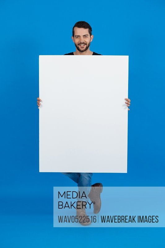 Handsome man holding a blank placard