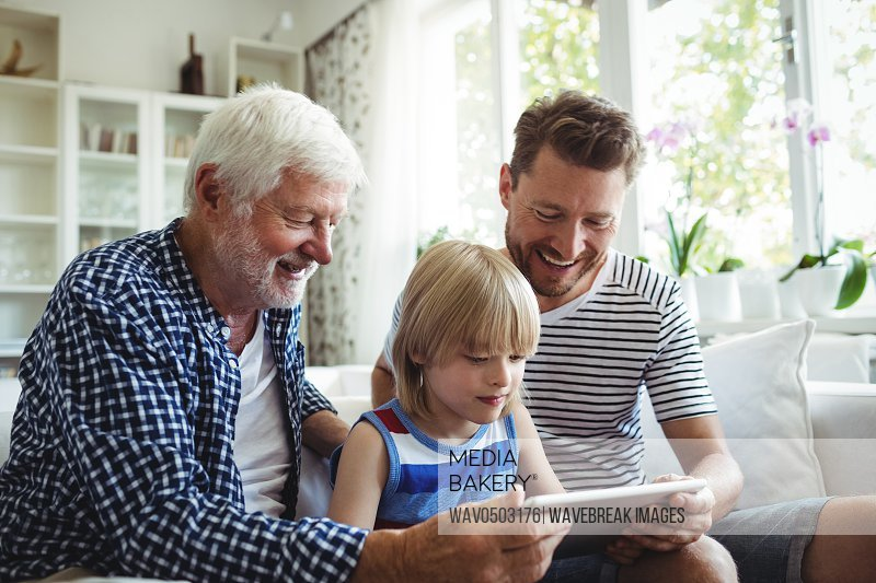 Boy using digital tablet with his father and grandfather in living room at home