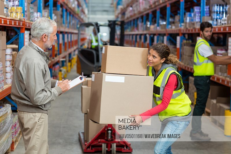 Warehouse manager noting on clipboard while female worker carrying cardboard boxes in warehouse
