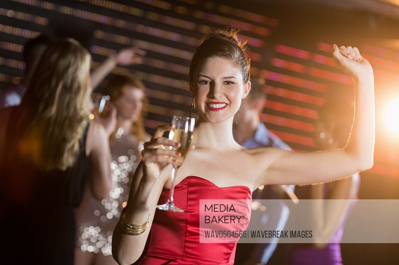 Portrait of young woman holding a glass of champagne while dancing in bar