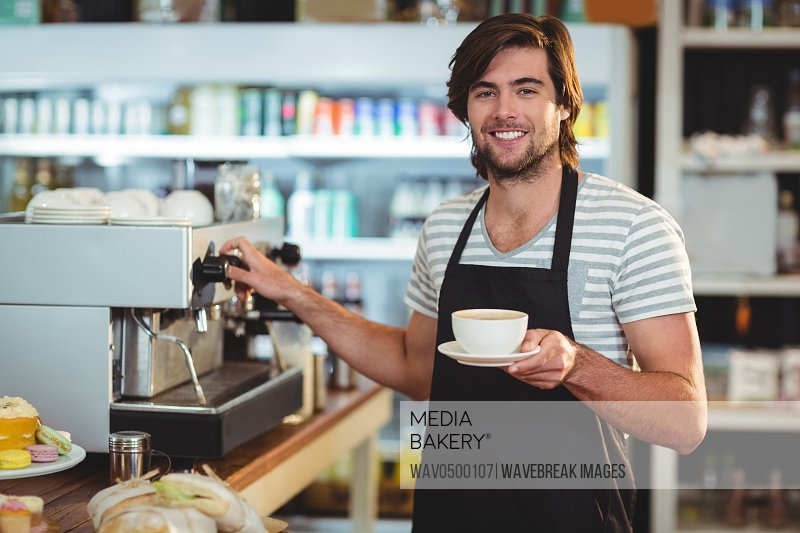 Portrait of smiling waiter holding cup of coffee in cafe