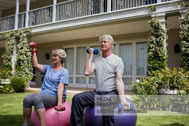 Senior couple exercising with dumbbells on fitness ball