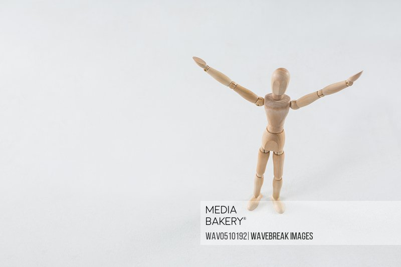 Wooden figurine standing on wooden floor with arms spread
