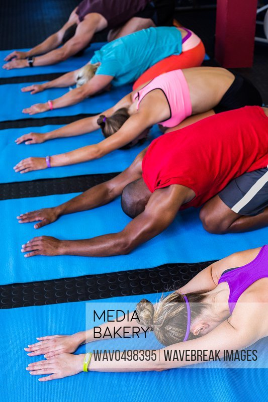 People doing stretching exercise while kneeling in gym