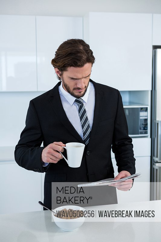 Businessman reading newspaper while having coffee in kitchen at home