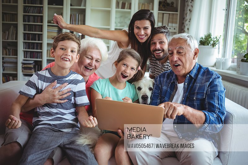 Portrait of happy multi generation using laptop at home