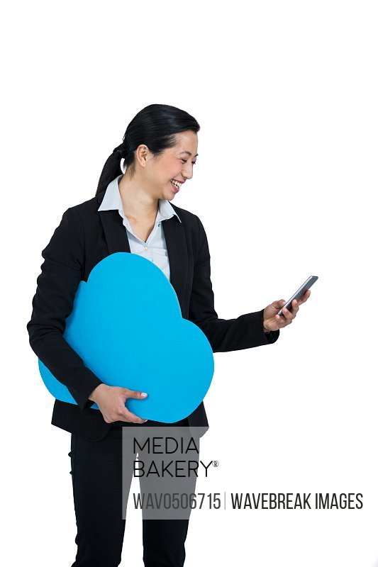 Smiling businesswoman holding cloud symbol and using mobile phone against white background