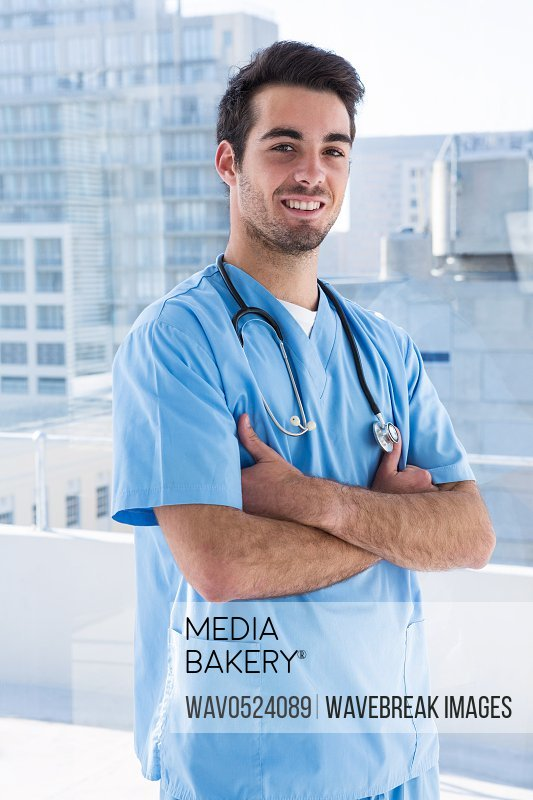Portrait of handsome surgeon standing with arms crossed
