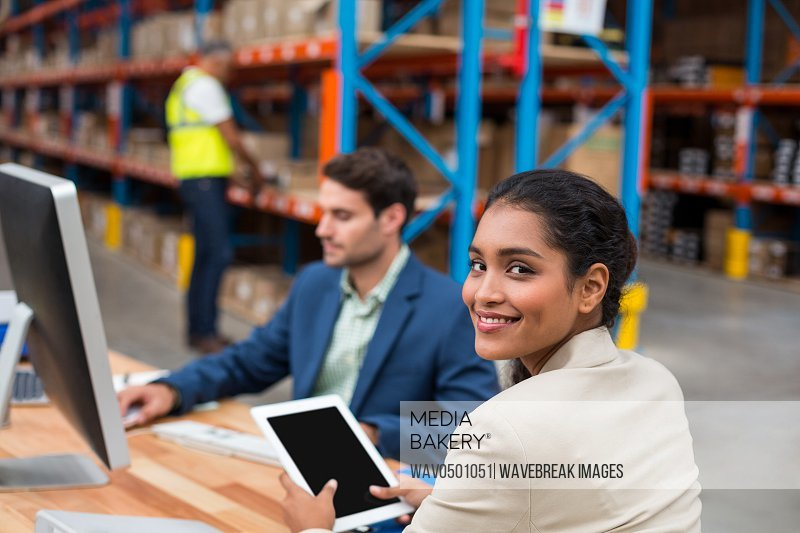 Portrait of smiling manager using digital tablet in warehouse office