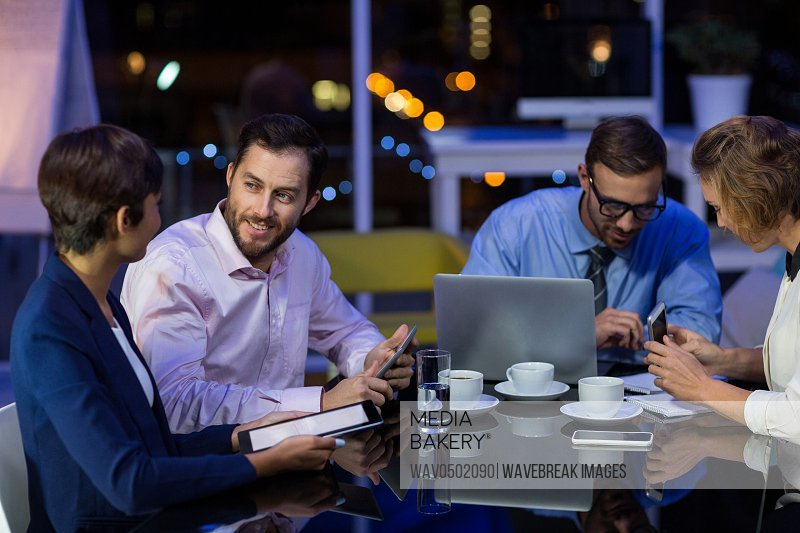 Businesspeople interacting with each other while working in office at night