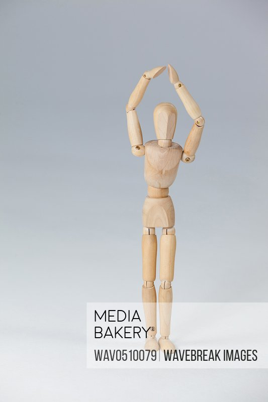 Wooden figurine standing with hands raised against white background