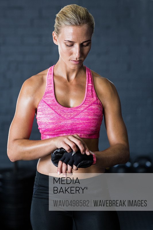 Young female athlete removing gloves while standing against wall in gym