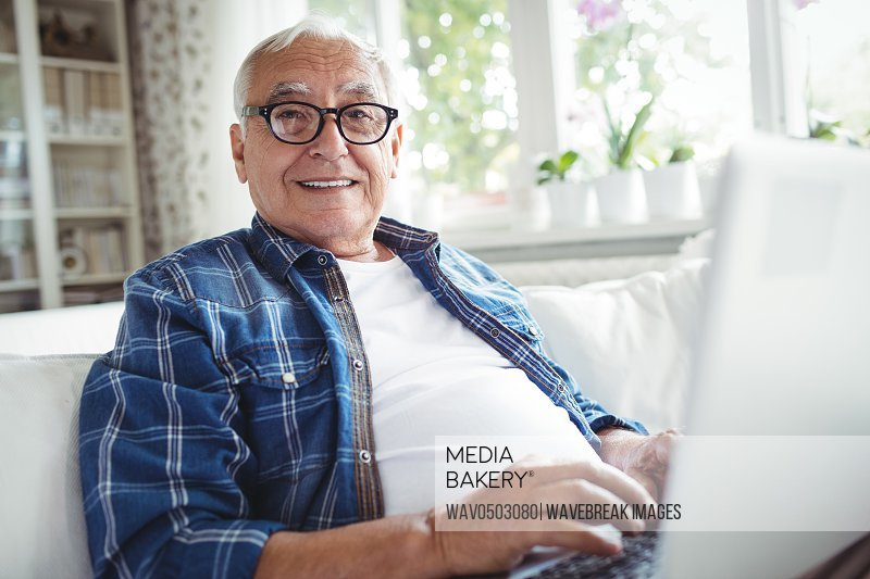Portrait of senior man using laptop at home