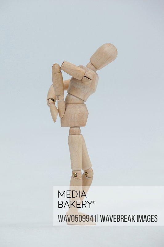 Wooden figurine standing with hands on back against white background