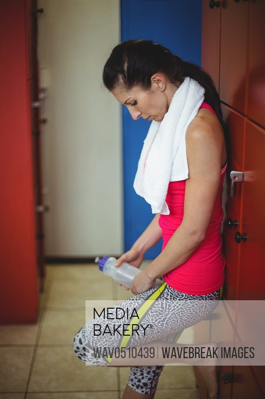 Woman holding water bottle standing in locker room after workout