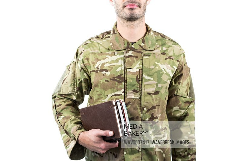 Mid section of soldier holding books against white background
