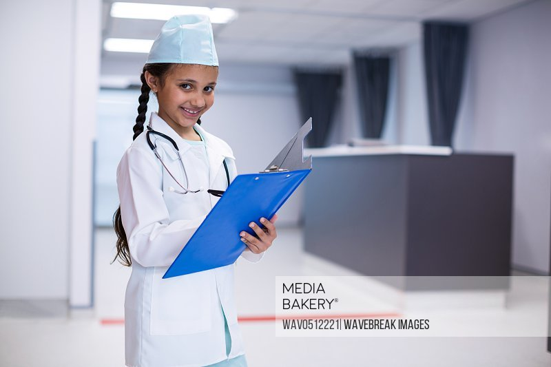 Girl writing on clipboard while pretending herself as a doctor in hospital