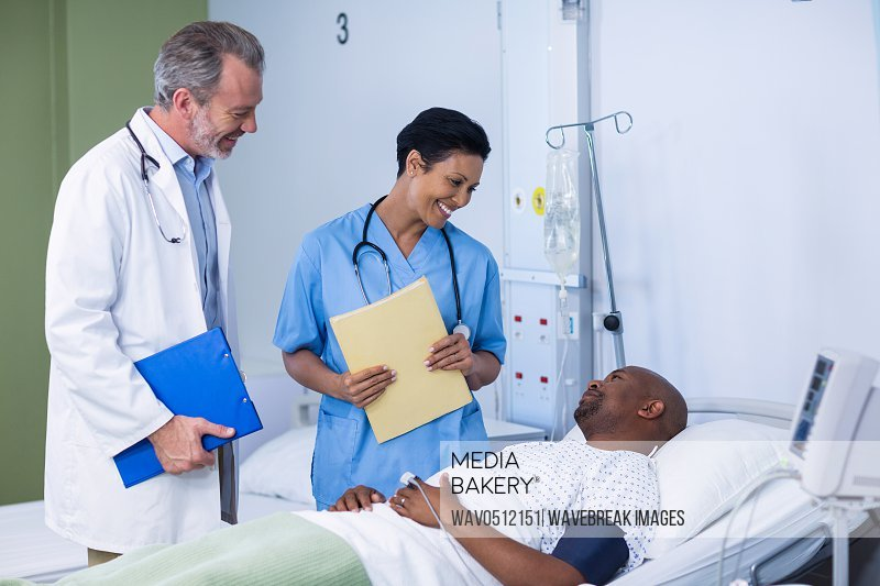 Doctor and nurse interacting with patient during visit in ward of hospital